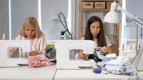 Seamstresses στην εργασία στο ράψιμο εργαστηρίων ντύνουν κοντά στη ράβοντας μηχανή, μπροστινή άποψη απόθεμα βίντεο