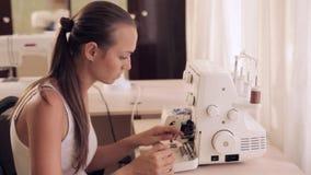 Seamstresses is threading needle on overlocke stock video footage