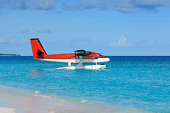 Seaplane anchoring on shore of turquoise ocean Royalty Free Stock Photography