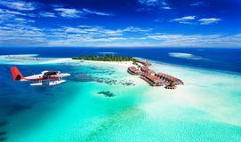 A seaplane approaching island in the Maldives. Aerial view of a seaplane approaching island in the Maldives royalty free stock image