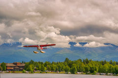 Seaplane flies over Lake Hood in Anchorage Alaska. Seaplane flies above Lake Hood after take off, climbing into higher altitude stock photography