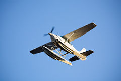 Seaplane in flight. Seaplane or floatplane in flight against blue sky, late sun Stock Photos