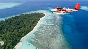 Seaplane flying above exotic iceland in Maldives. Stock Photography