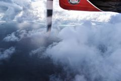 Seaplane flying through the clouds over Maldive island ocean. Aerial view from a seaplane flying through the clouds over Maldive island ocean sea for holiday Stock Photos