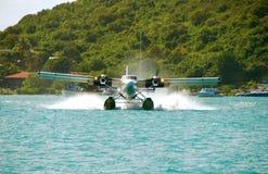 Seaplane landing. Flying boat landing in the water near exotic island stock photo