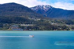 Seaplane landing in the water near a small city in Alaska royalty free stock images