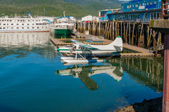 Seaplane at marina with fishing vessels Stock Image