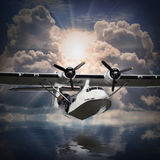 The seaplane. Old rescue seaplane flying against sunset over a sea level Royalty Free Stock Photo