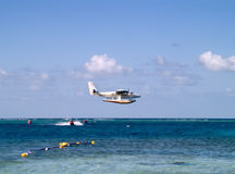 Seaplane Over Speeding Jetski. Young man enjoying a fast ride on a jetski in the blue Caribbean water Stock Photo