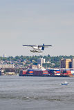 Seaplane preparing for water landing at container harbor Stock Image