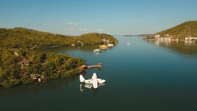 Seaplane on sea water surface. Aerial white Seaplane in the sea bay. hydroplane on the water surface near the shore Travel concept, Aerial footage stock footage