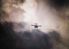 Seaplane in stormy sky. Silhouetted seaplane flying in stormy sky background Royalty Free Stock Images