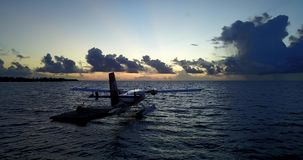 Seaplane at sunset sunrise in maldives with view from aerial drone on purple blue sea ocean water and sky stock video