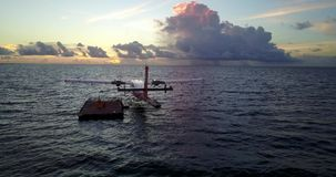 Seaplane at sunset sunrise in Maldives with view from aerial drone on purple blue sea ocean water and sky stock video footage