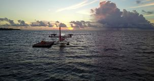 V09255 seaplane at sunset sunrise in maldives with view from aerial drone on purple blue sea ocean water and sky. Seaplane at sunset sunrise in maldives with stock video
