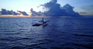 V09284 seaplane at sunset sunrise in maldives with view from aerial drone on purple blue sea ocean water and sky. Seaplane at sunset sunrise in maldives with stock footage