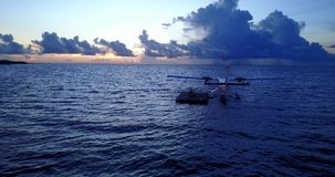 V09269 seaplane at sunset sunrise in maldives with view from aerial drone on purple blue sea ocean water and sky. Seaplane at sunset sunrise in maldives with stock video footage