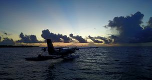 V09273 seaplane at sunset sunrise in maldives with view from aerial drone on purple blue sea ocean water and sky. Seaplane at sunset sunrise in maldives with stock video