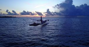 V09257 seaplane at sunset sunrise in maldives with view from aerial drone on purple blue sea ocean water and sky. Seaplane at sunset sunrise in maldives with stock video
