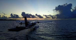 V09285 seaplane at sunset sunrise in maldives with view from aerial drone on purple blue sea ocean water and sky. Seaplane at sunset sunrise in maldives with stock video footage