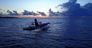 V09261 seaplane at sunset sunrise in maldives with view from aerial drone on purple blue sea ocean water and sky. Seaplane at sunset sunrise in maldives with stock footage