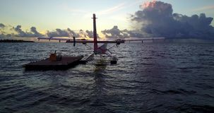 V09262 seaplane at sunset sunrise in maldives with view from aerial drone on purple blue sea ocean water and sky. Seaplane at sunset sunrise in maldives with stock video footage
