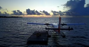 V09278 seaplane at sunset sunrise in maldives with view from aerial drone on purple blue sea ocean water and sky. Seaplane at sunset sunrise in maldives with stock video