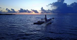 V09258 seaplane at sunset sunrise in maldives with view from aerial drone on purple blue sea ocean water and sky. Seaplane at sunset sunrise in maldives with stock video footage