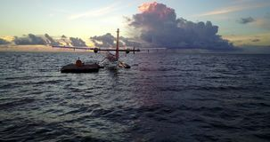 V09251 seaplane at sunset sunrise in maldives with view from aerial drone on purple blue sea ocean water and sky. Seaplane at sunset sunrise in maldives with stock video footage