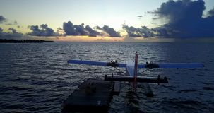 V09292 seaplane at sunset sunrise in maldives with view from aerial drone on purple blue sea ocean water and sky. Seaplane at sunset sunrise in maldives with stock video