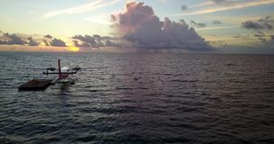 V09250 seaplane at sunset sunrise in maldives with view from aerial drone on purple blue sea ocean water and sky. Seaplane at sunset sunrise in maldives with stock video