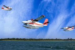 Seaplanes flying over Maldive islands beach. Seaplanes flying through the clouds over Maldive island beach ocean sea for holiday background Stock Photos