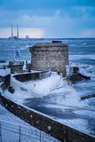 Seapoint Martello Tower. county Dublin. Ireland. Seapoint Martello Tower and Poolbeg chimneys covered with snow during storm Emma, Dun Laoghaire. county Dublin Royalty Free Stock Images