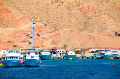 The seaport in Egypt, pier. Many white yachts in the sea, near big rock Stock Photo