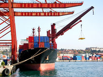 Seaport with freighter and cranes. A cargo ship under container cranes seen from above Stock Photo