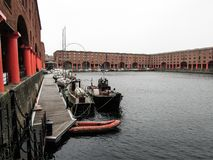 Seaport in Liverpool surrounded by mid range buildings made out of red brick. Grey sky with clouds showing a typical rainy day in England stock image