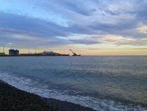 Seaport Sochi, sea and clouds at sunset. Seaport Sochi at sunset. Black Sea coast and beautiful clouds. Travel Russia, resort Sochi Stock Photos