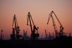A seaport at sunset, with three cranes Royalty Free Stock Photos