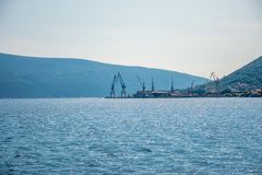 In the seaport there is unloading of ships with large cranes. Royalty Free Stock Images