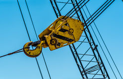 Seaport tower crane hook. Close view of yellow hook of tower crane Royalty Free Stock Images