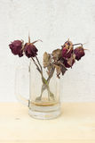 Sear red rose in glass on plywood background and concrete wall. Picture stock photos