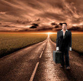 Search. Business man walking with a suitcase on the road Royalty Free Stock Photo