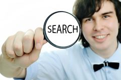 Search. A young man with a magnifier with word ''search'' in it stock photo