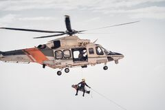 Free Search And Rescue SAR Helicopter Team Hoists An Injured Person Stock Images - 188078674