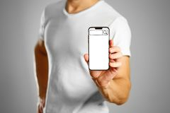 Search bar on the phone screen. A man holding a black smartphone. With a white blank screen. Smartphone with large screen. Close up. Isolated background royalty free stock images