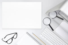 Search concept, desk with magnifying glass,computer and blank board Royalty Free Stock Photography