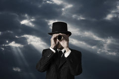 Search in darkness. Business man looks through a telescope in darkness Royalty Free Stock Photos