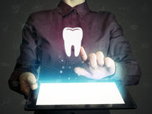 Search for dentists, dental services, consultations. Image of a girl with tablet pc in her hands and tooth icon. Search for dentists, dental services royalty free stock photography