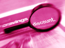 Search for discount. Up for grabs - A concept image of a magnifier focused on the word discount on the newspaper. simple composition with copy space Royalty Free Stock Photography