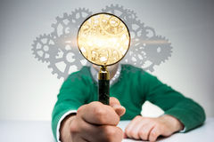 Search engine concept. With man covering face with golden gear mechanism inside magnifier Royalty Free Stock Photography